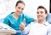 Man in dental chair giving thumbs up.