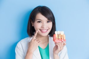 smiling woman holds jaw model with dental implants